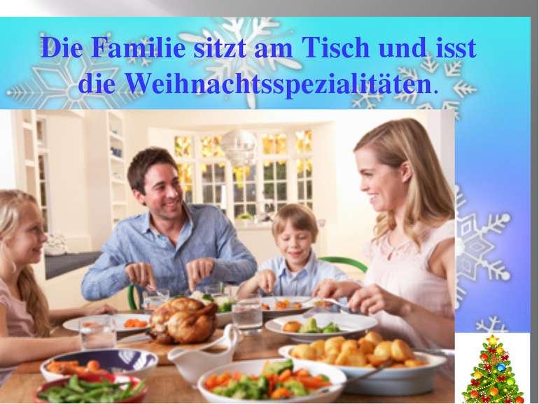 Die Familie sitzt am Tisch und isst die Weihnachtsspezialitäten.