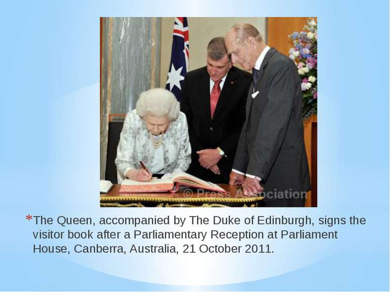 The Queen, accompanied by The Duke of Edinburgh, signs the visitor book after...