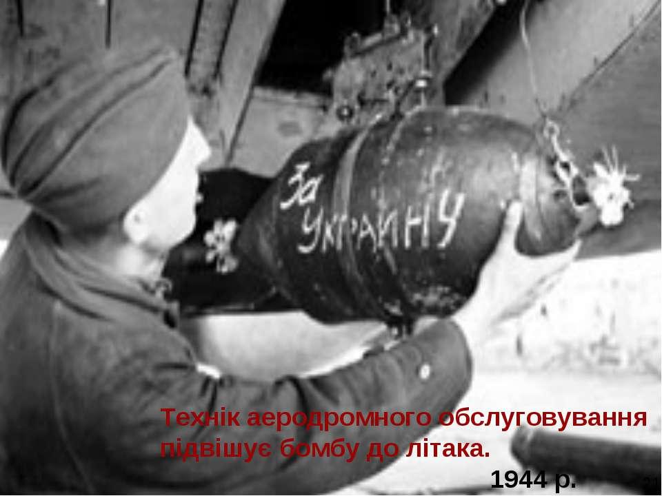 Технік аеродромного обслуговування підвішує бомбу до літака. 1944 р. 21